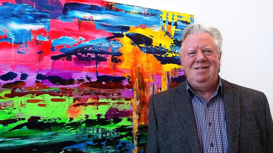 Mike Hunnicut standing in front of one of his more vivid pieces of art displayed in the Wings Gallery at the College of DuPage on Dec. 3rd, 2014.