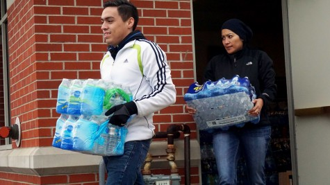 Volunteers Araceli Contreras (left) and Missael Sanchez (right) carrying water to the front of the Henry J. Hyde Resource Center on Jan. 30.