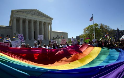 In this April 28, 2015 file photo, demonstrators stand in front of a rainbow flag of the Supreme Court in Washington as the Supreme Court was set to hear historic arguments in cases that could make same-sex marriage.