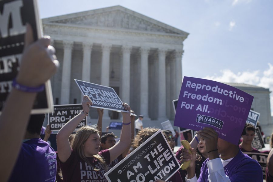 WASHINGTON%2C+DC+-+JUNE+25%3A+Abortion+opponents+and+supporters+hold+signs+in+front+of+the+U.S.+Supreme+Court+on+June+25%2C+2018+in+Washington%2C+DC.+The+high+court+is+expected+to+issue+decisions+in+six+remaining+cases%2C+including+the+travel+ban%2C+public+sector+unions+and+redistricting%2C+ahead+of+their+end-of-June+deadline+this+week.++%28Photo+by+Zach+Gibson%2FGetty+Images%29