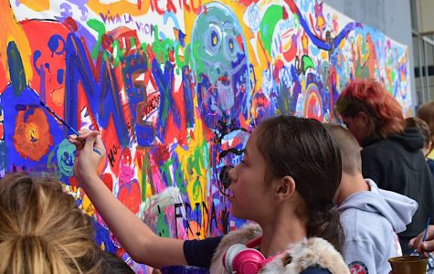 Adults and children alike gathering to contribute to the community mural.